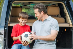 Father and son sit near car with opened boot and going to talk a