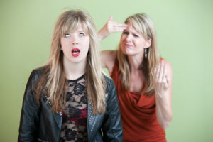 Frustrated mother behind angry daughter in provocative clothing