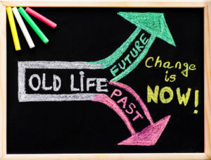 Change is now, handwriting with chalk on wooden frame blackboard, colored chalk in the corner, lifestyle change concept