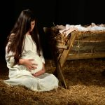 the-nativity-through-an-adoption-lens-part-2.Pregnant Mary holding stomach at manger on Christmas Eve