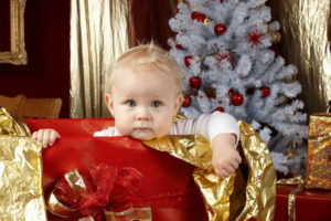 Baby looking out from a giftbox near a Christmas tree