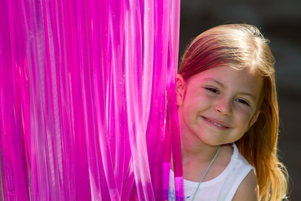 Girl smiling next to luminous pink lighting tubes