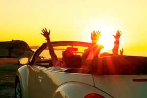 Happy family  in a cabriolet convertible car at the sunset in summer