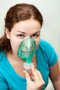 Woman in medical inhalation mask breathing