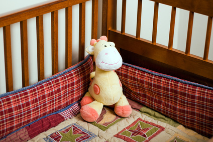 Yellow stuffed animal giraffe in empty baby crib