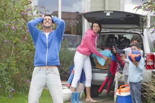 Frustrated father shouting as family packs car for vacation